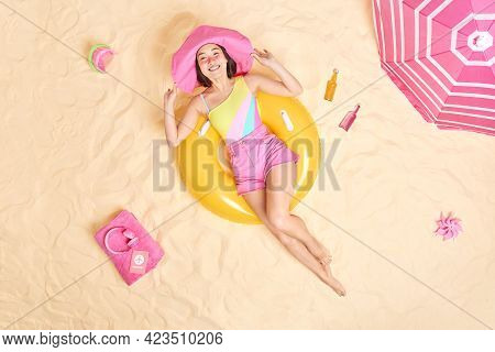 Unforgettable Vacation. Relaxed Young Asian Woman Poses In Swim Ring Wears Sunhat Swimsuit And Short