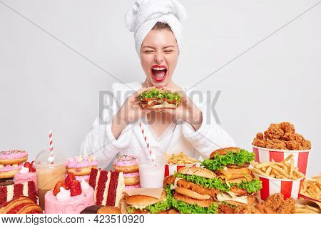 Cheat Mea And Gluttony. Funny Young Woman Exclaims Loudly Keeps Mouth Wide Opened Eats Tasty Burger