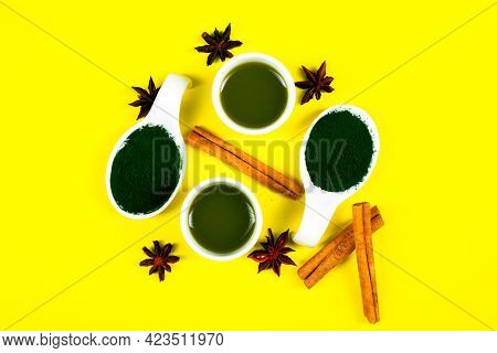 White Spoon With Spirulina Powder On Yellow Background, Cinnamon Sticks And Star Anise