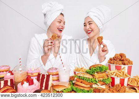Two Happy Diverse Women Look Gladfully At Each Other Hold Nuggets Eat Tasty Fast Food Enjoy Cheat Me