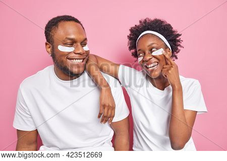 Indoor Shot Of Happy Carefree Black Woman And Man Looks With Smile At Each Other Apply Beauty Patche