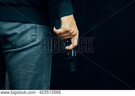Dangerous Pistol In Person Hand. Man In Sweater And Jeans Is Holding Gun. Criminal With Revolver On