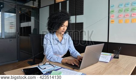 Young African American Focused Female Ceo Data Analyst Businesswoman Sitting At Desk Working Typing