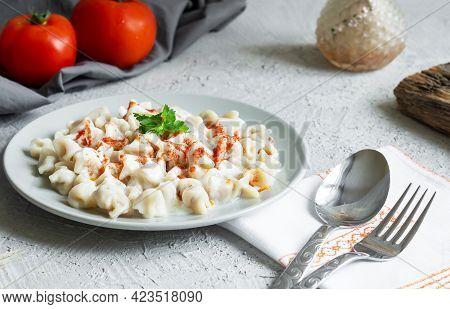 Turkish Traditional Food Ravioli With Yoghurt And Tomato Sauce In Plate, Manti