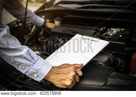 Car Care Maintenance And Servicing, Close-up Hand Technician Auto Mechanic Using Checklist After Rep