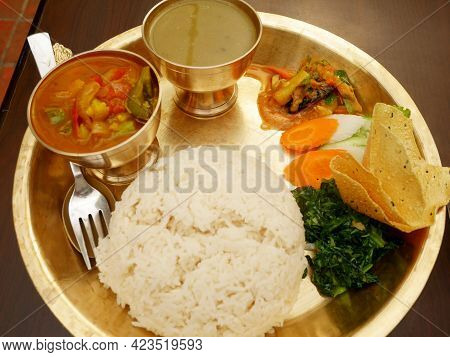 Nepalese Local Food Set And Water Drinks On Retro Vintage Brass Plate Set For Serve Lunch Meal To Ne