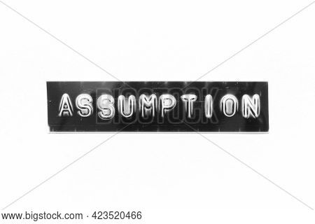 Embossed Letter With Word Assumption In Black Banner On White Paper Background