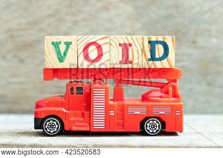 Fire Ladder Truck Hold Letter Block In Word Void On Wood Background