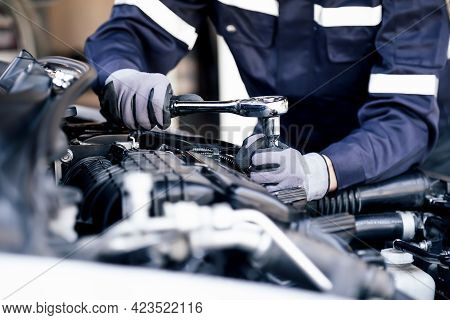 Professional Mechanic Working On The Engine Of The Car In The Garage. Car Repair Service. The Concep