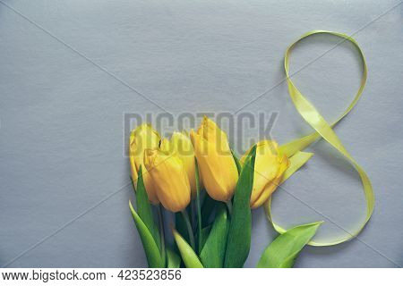 Five Yellow Fresh Tulips On A Grey Background. Flowers With The Number Eight Made Of Ribbon. Concept
