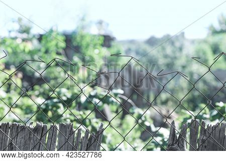An Old Dilapidated Fence In The Country Between Neighboring Gardens. Fencing A Vegetable Garden In T