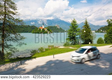 Motion Blured White Electric Car In Front Of Bled Lake, Country Of Slovenia. Travel, Tourism, Explor