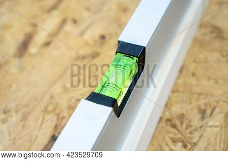 Water Level Tool Lying On The Osb Sheet. Spirit Level Bubble Shows The Ideal Parameter.