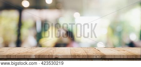 Empty Wood Table And Blurred Light Table In Coffee Shop And Cafe With Bokeh Background. Product Disp