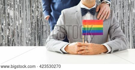 homosexuality, same-sex marriage and lgbt concept - close up of happy male gay couple in suits and bow-ties with wedding ring holding rainbow flag over foil party curtain on background