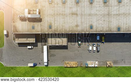 Aerial. Transportation And Logistics. Truck And Lorries Unloading At A Large Warehouse. Top View Fro