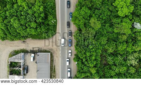 Aerial. Car Traffic On The Narrow Roadway Between Green Trees. Top View From Drone.