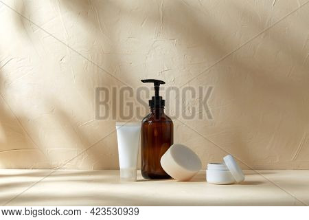 beauty, cosmetics and object concept - bottle of shower gel, soap, body scrub and moisturizer on beige surface with shadows