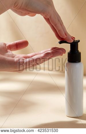 beauty, cosmetics and bodycare concept - close up of hands with bottle of body lotion over beige background with shadows