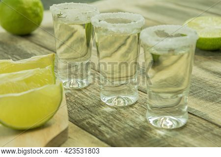 The Glasses Are Filled With Tequila And Lime And Salt. Aged Tequila And Lime Stacks. Background With