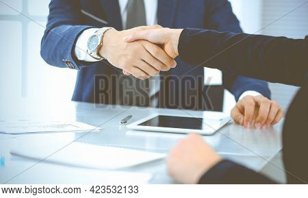 Businesspeople Or Lawyers Shaking Hands Finishing Up A Meeting In Blue Toned Office , Close-up. Succ