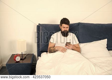 Going Online. Bearded Man Use Smartphone In Bed. Technology For Home. Adoption Of Mobile Technology.