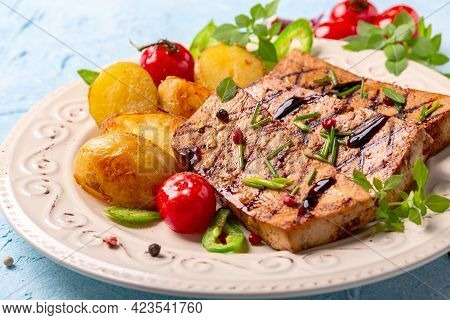 Grilled Tofu Steaks And New Potatoes Are Served With Cherry Tomatoes, Green Onions And Peppers On A