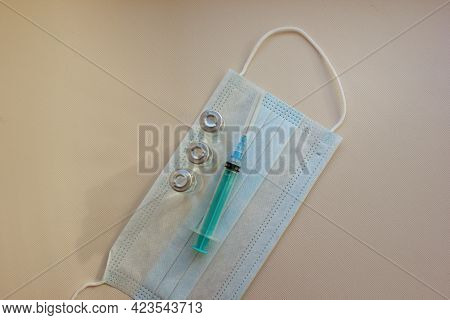 Syringe With Needle And Vials With Medicine Lies On Medical Mask On Light Background. Vaccination. C