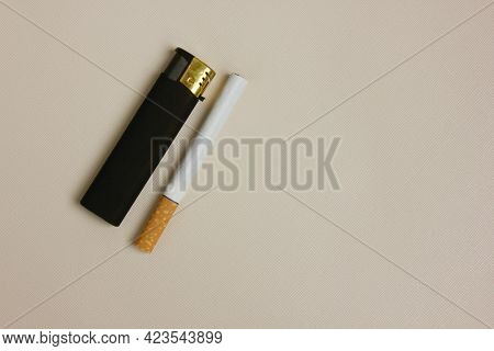 Black Plastic Gas Lighter And Cigarette, Isolated On A White Background. Harm To Health. The Concept