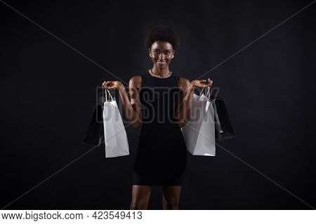 African American Woman With Afro Hairstyle Holds Black And White Shopping Bags. Sale And Discounts B