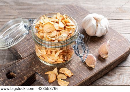 Dried Garlic Flakes Or Garlic Chips And Raw Garlic On Old Wooden Background