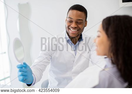 Black Dentist Doctor Holding Mirror, Showing Result Of Teeth Treatment To Patient