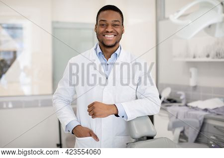 Portrait Of Young Smiling Stomatologist Posing In Dental Clinic Interior
