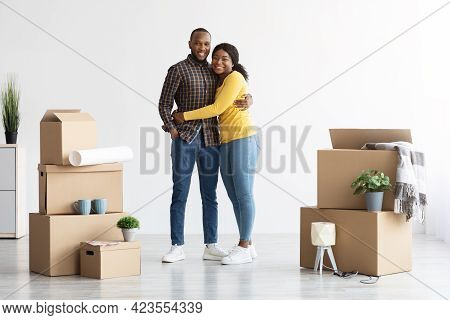 Portrait Of Happy African American Spouses Standing Among Cardboard Boxes After Moving