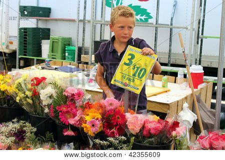 Boy is selling flowers at the farmer's market