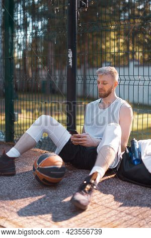 Basketball Player Cool Guy Having Break After Training Sitting With Phone On Court Outdoors In Summe