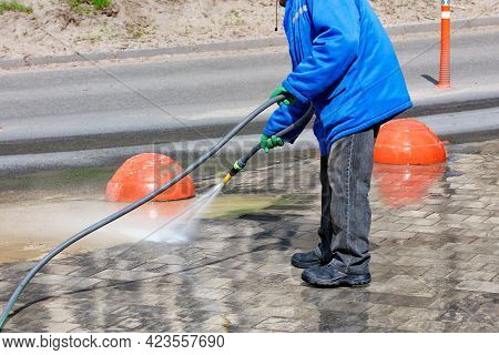 A Janitor In A Blue Jacket With A Water Hose Washes The Dirt On The Side Of The Road On A Sunny Day.