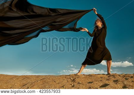 Feeling of flight, dreams. Beautiful romantic girl in a long black dress posing in the desert with a scarf fluttering in the wind. Sky background.