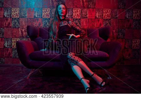 Beautiful young woman in black evening dress sits on a sofa in luxury apartments. Glamorous lifestyle. Beauty, fashion. Modern interior, furniture.