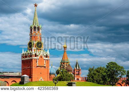 Moscow Kremlin In Summer, Russia. View Of Spasskaya Tower Of Kremlin And St Basil's Cathedral On Sky