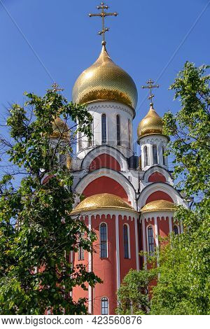 Temple With Golden Domes On A Background Of Green Leaves. Christian Temple, Faith Concept