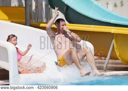 Happy Man And Little Girl Ride Slide In Water Park