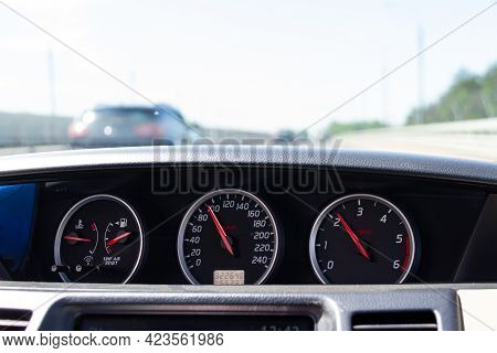 Close-up Of A Car Dashboard. Blurred View Of The Road With Moving Cars Through The Windshield.