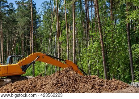 The Excavator Prepares The Site For The Construction Of The Road. Orange Construction Machinery Agai