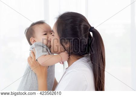 Young Asian Mother Holding Little Baby Girl And Kiss Together In The Bedroom At Home, Mom Carry Chil