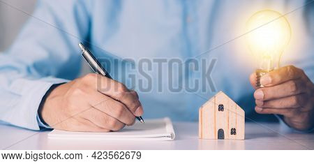 Businessman Holding Light Bulb While Home Wooden For Solution Innovation And Environment, Thinking I