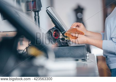 Process Of Barcode Scanning On A Goods In A Shop, Saleswoman Selling A Handbag To A Customer