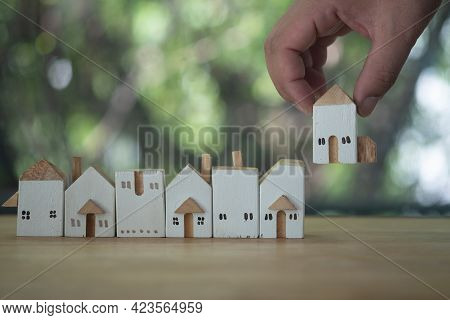 Close Up Hand Choosing Mini Wood House Model From A Row Model. Choose What's The Best. A Symbol For