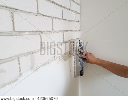 Laying Gypsum Tiles On Plaster Glue The Wall With A Putty Knife