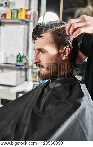 Handsome brunet man visiting hairstylist in barbershop. Men's beauty and style.